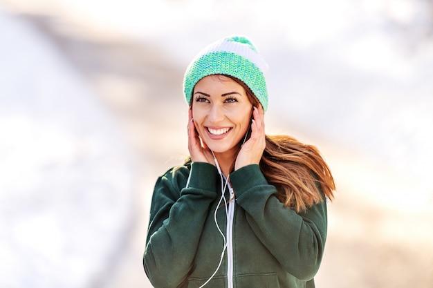 ビーニーと屋外で休んでいる間音楽を聴くスポーツウェアで美しい白人ブルネットのクローズアップ。冬のフィットネスの概念。