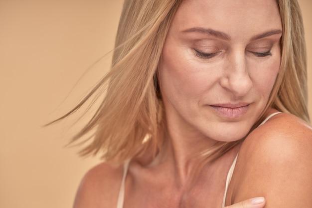 스튜디오에서 포즈를 취하고 내려다보고 있는 아름다운 백인 성숙한 여성의 클로즈업