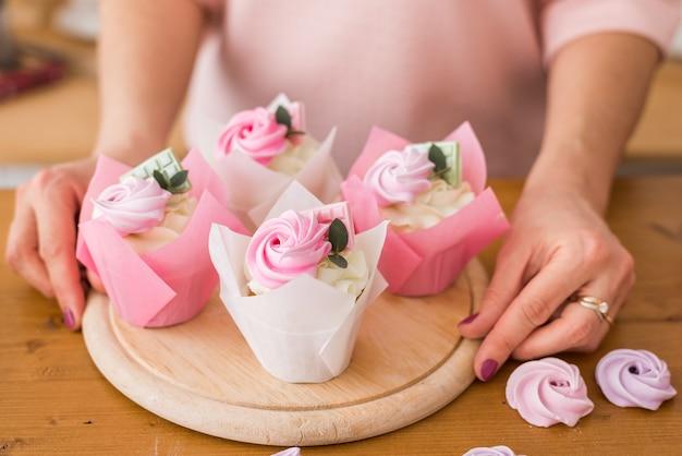 美しいカップケーキのクローズアップ。お祝いパッケージのクリームとチョコレートの自家製カップケーキ
