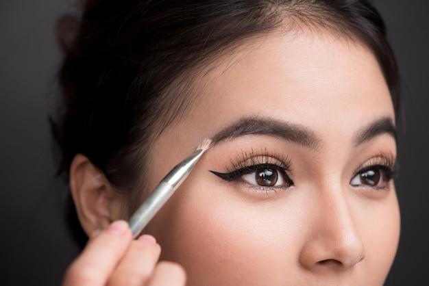 화장을 하는 젊은 아시아 여성의 아름다운 얼굴을 클로즈업하세요. 작가가 브러시로 눈썹에 아이섀도를 바르고 있다