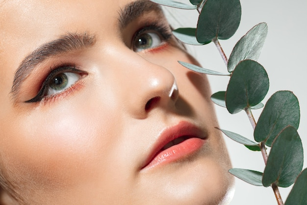Закройте красивое женское лицо с зелеными листьями растений на белом фоне. концепция косметики, макияжа, натуральных и экологических процедур, ухода за кожей. блестящая и здоровая кожа, мода, здравоохранение.
