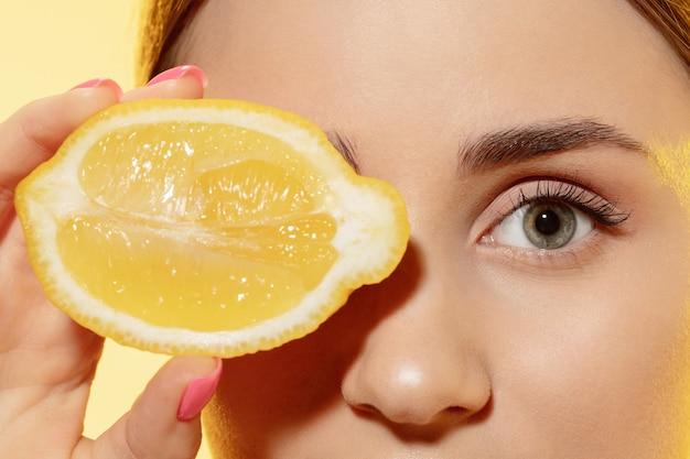 Крупным планом красивое женское лицо с ломтиком лимона на желтом фоне косметика и макияж