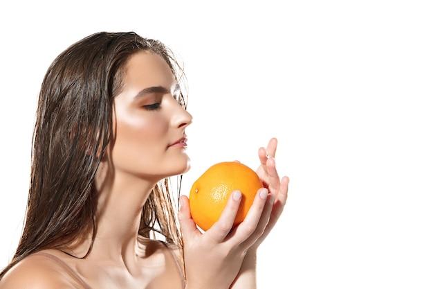 Крупным планом красивое женское лицо с апельсином на белом фоне, косметика и макияж, натуральный и