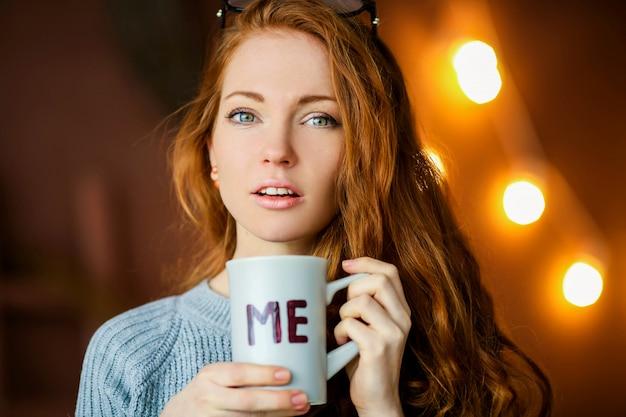 コーヒーカプチーノの大きなガラスのコップを保持している美しい女性の手のクローズアップ。暖かい冬のニットの白いセーターを着ている女性