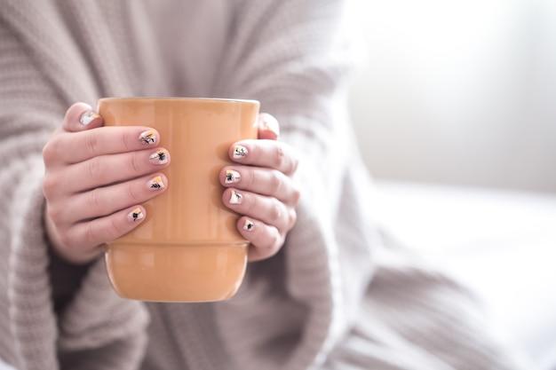 カプチーノコーヒーと花の大きな白いカップを保持している美しい女性の手のクローズアップ。暖かい冬を着ている女性は赤いセーターを編んだ。トーン。
