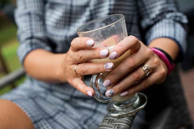카푸치노 커피의 큰 흰색 컵을 들고 아름 다운 여성의 손을 닫습니다 회색 드레스를 입고 여자