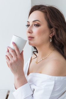 카푸치노 커피의 큰 흰색 컵을 들고 아름 다운 여성의 손을 닫습니다.