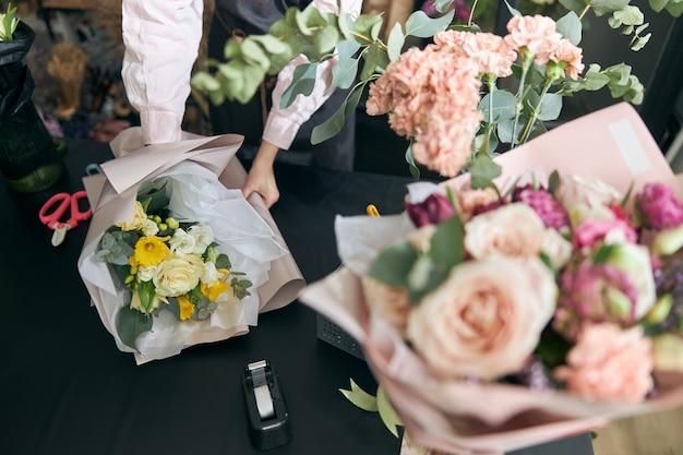 フラワーショップ、コピースペースのテーブルに横たわっている美しい花のクローズアップ。ライフスタイルフラワーショップ。美しい花の構成。