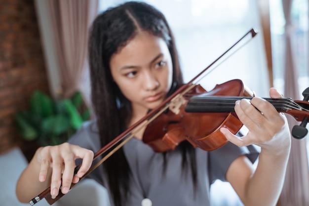Крупным планом красивая девушка играет на скрипке