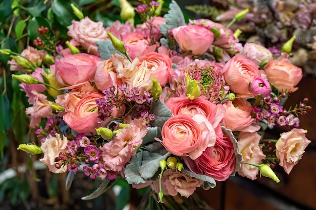お店でバラや他の花を混ぜた美しいマルチカラーの花束のクローズアップ。切り花。