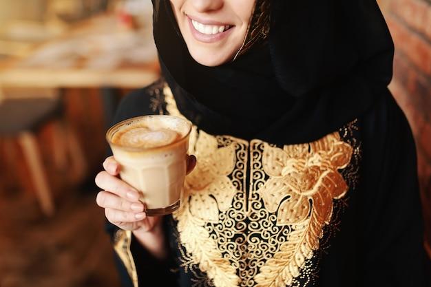 카페테리아에 앉아서 커피를 즐기는 전통적인 착용에 아름 다운 이슬람 여자의 닫습니다.