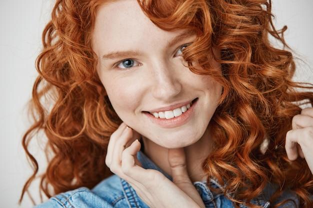 Крупным планом красивая натуральная рыжая девушка с веснушками улыбается