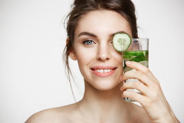 白い背景の上にキュウリのスライスと水のガラスを保持しているカメラを見て笑っている美しい裸の女の子のクローズアップ。健康的な栄養。美容とスキンケア。