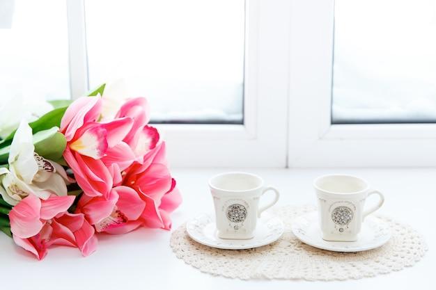 花瓶の美しい赤いチューリップと窓枠の2つのカップのクローズアップ。