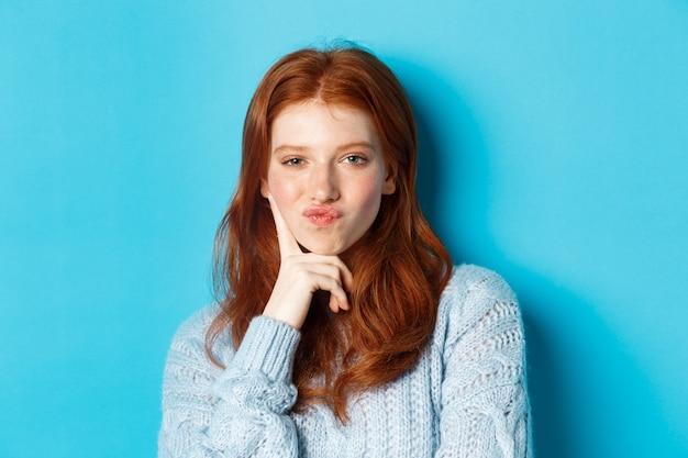 Крупным планом красивая рыжая девушка думает, морщит губы и смотрит вдумчиво в камеру, делая выбор, стоя на синем фоне.