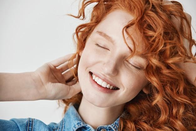 Крупным планом красивая рыжая молодая девушка улыбается с закрытыми глазами