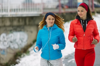 Close-up of beautiful two female athlete running in winter