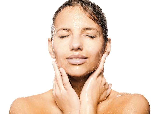 Крупным планом лицо красивой мокрой женщины с каплей воды