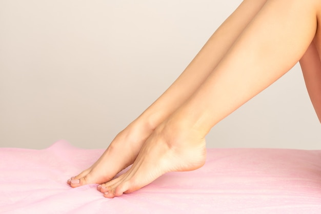 분홍색 침대 시트에 제모 후 아름다운 흰색 부드러운 여성 다리 또는 발을 닫습니다