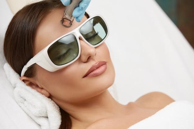 보호 안경을 착용하는 그녀의 이마에 레이저 절차를 수행하는 아름다운 여자의 근접, 뷰티 살롱에서 레이저 피부 절차를받는 예쁜 여성
