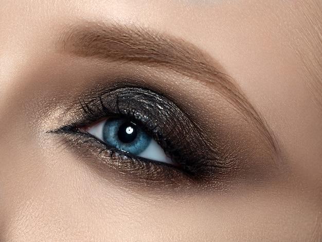 Крупным планом глаза красивой женщины с бронзовым макияжем smokey eyes
