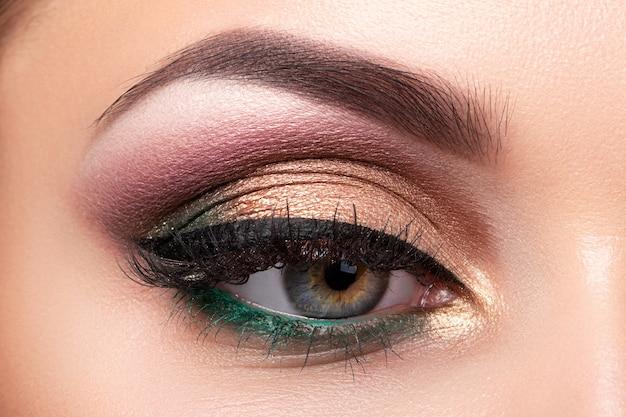 色とりどりのスモーキーアイメイクで美しい女性の目のクローズアップ。現代のファッションが構成しています。