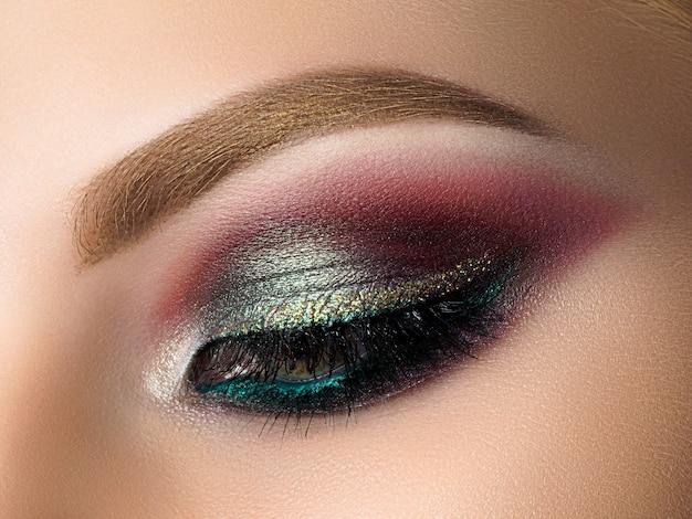 色とりどりのスモーキーアイメイクで美しい女性の目のクローズアップ