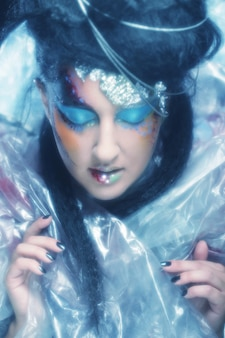 クリエイティブなファッションアートメイクで美しい女性の顔のクローズアップ。スタジオショット。