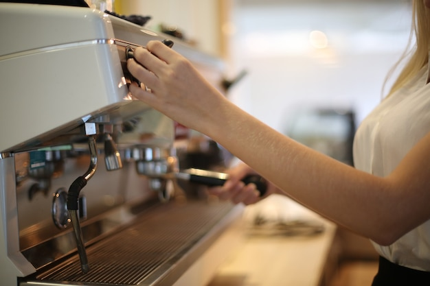 Крупный план красивой женщины, использующей кофеварку на кухне