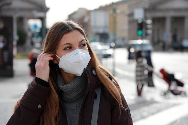 屋外の冬服で横を向いているffp2kn95防毒マスクを身に着けている美しい女性のクローズアップ