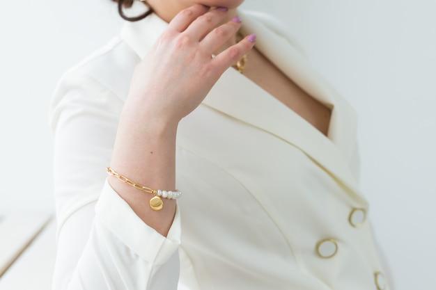 목걸이와 진주 팔찌를 착용하는 아름 다운 여자의 클로즈업. 액세서리, 보석 및 보석류 개념.