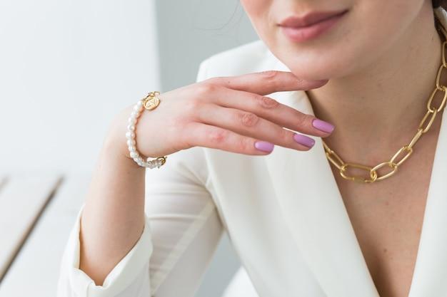 ネックレスと真珠のブレスレットを身に着けている美しい女性のクローズアップ