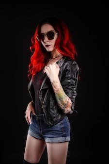 Крупным планом красивая женщина с татуировкой в джинсах короткая краска против черного