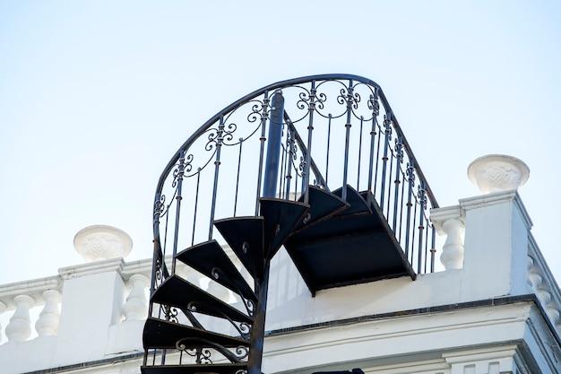 집 옆에 있는 아름다운 연철 외부 나선형 계단을 닫습니다