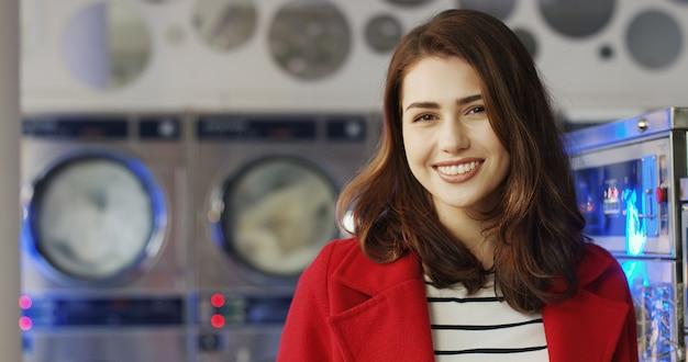 ランドリーサービスルームのカメラに元気よく笑っている赤いコートの美しい若い白人女性のクローズアップ。洗濯機で笑ってかなり幸せな少女の肖像画。