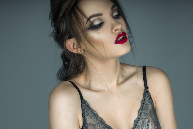 Крупным планом красивая молодая девушка с сексуальными красными губами и макияжем позирует в кружевном бюстгальтере в студии