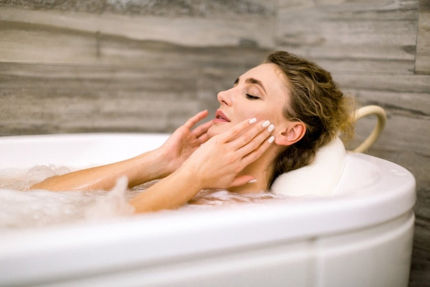 ビューティーセンターの温泉でリラックス、顔に触れる、笑顔の美しい若い女性のクローズアップ