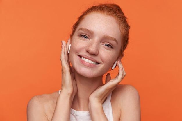 오렌지 배경 위에 서있는 그녀의 귀에 이어폰에 손을 올리는 매듭에 그녀의 여우 같은 머리를 입고 매력적인 미소로 카메라를보고 아름다운 젊은 빨간 머리 여성의 근접