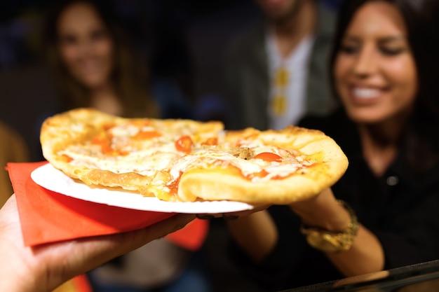 通りの飲食店でピザを訪れて購入する美しい若い女性と彼女の友人のクローズアップ。