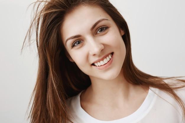 Крупный план красивой молодой женщины, выглядящей счастливой, улыбаясь с белыми зубами
