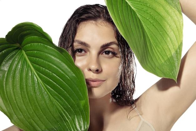 白い壁の上の美しい若い女性のクローズアップ。ツヤと健康な肌