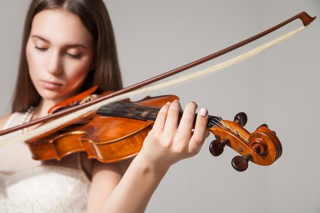 Крупный план красивой молодой женщины, играющей на скрипке