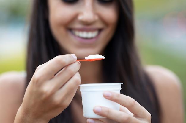 通りに立っているアイスクリームを食べながら笑っている美しい若い女性のクローズアップ。