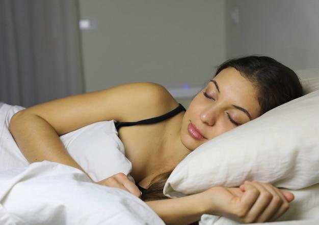 집에서 그녀의 침대에서 자고있는 동안 웃고있는 아름다운 젊은 여성의 닫습니다
