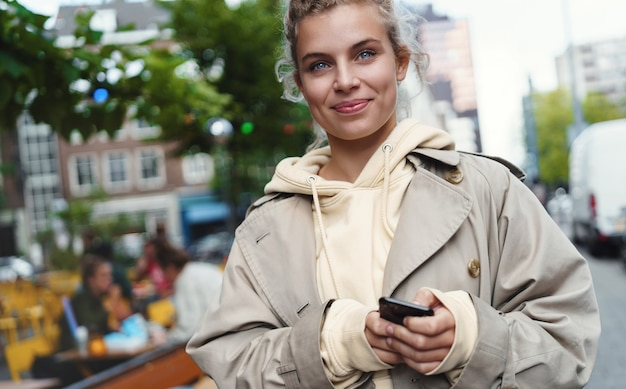 휴대 전화와 함께 거리에 서 서 행복 하 게 웃는 아름 다운 젊은 여자의 클로즈업.