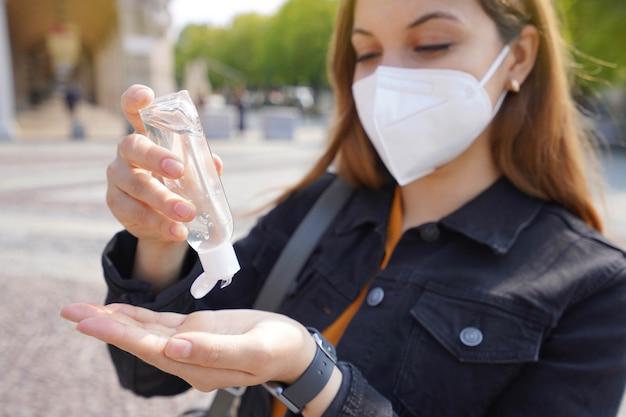 도시 거리에서 그녀의 손을 소독하는 알코올 젤을 사용하여 kn95 ffp2 보호 마스크를 착용하는 아름다운 젊은 여성의 닫습니다. 손에 집중하십시오.