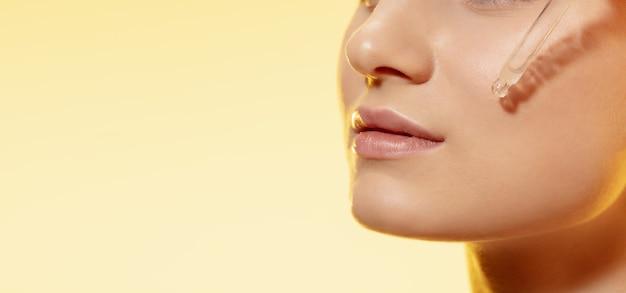 Закройте красивой молодой женщины с эфирным маслом на желтом фоне. концепция косметики, макияжа, натуральных и экологических процедур, ухода за кожей. блестящая и здоровая кожа, мода, здравоохранение.