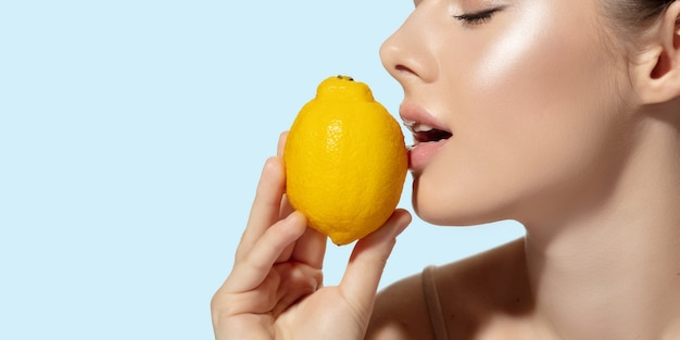 白い背景の上の新鮮なレモンと美しい若い女性のクローズアップ。化粧品、メイクアップ、ナチュラル&エコトリートメント、スキンケアのコンセプト。光沢のある健康な肌、ファッション、ヘルスケア。コピースペース。