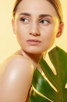 白い背景の上の緑の葉を持つ美しい若い女性のクローズアップ。化粧品、メイクアップ、ナチュラル&エコトリートメント、スキンケアのコンセプト。光沢のある健康な肌、ファッション、ヘルスケア。