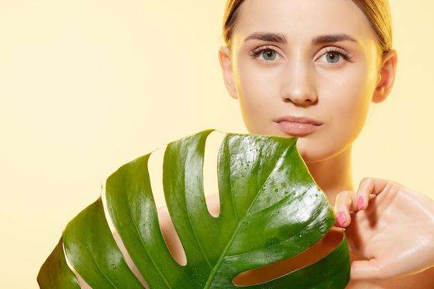 白い背景の上の緑の葉を持つ美しい若い女性のクローズアップ